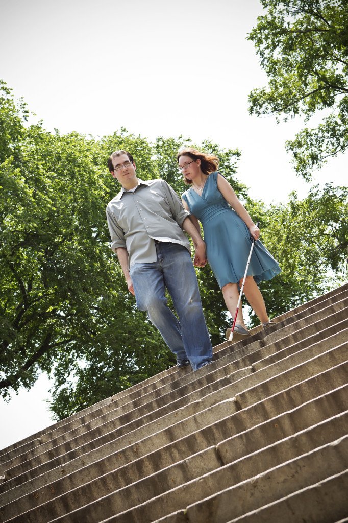 woman carrying white cane walks down stairs hand in hand with a man. A beautiful blue sky and bright sun behind them.